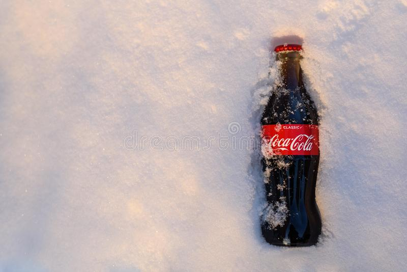 Kazan Ryssland, mars, 17, 2018: Original- glasflaska av cocaen - fryst cola klibbade i den insnöade ljusa solnedgången royaltyfria bilder