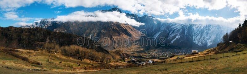 Kazbegi Stepantsminda en Gergeti tegen de bergen van de Kaukasus georgië stock afbeelding