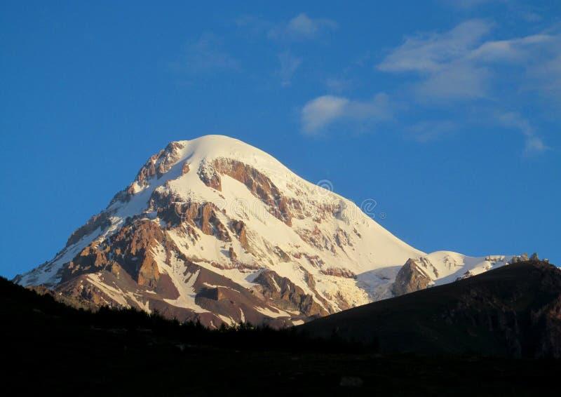 Kazbekberg met sneeuw in Kaukasische bergen in Georgië wordt behandeld dat royalty-vrije stock fotografie