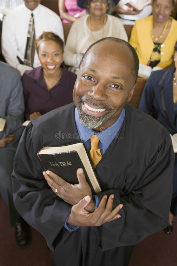 Kaznodzieja Trzyma Świętą biblię Z kongregaci obsiadaniem W kościół zdjęcia royalty free