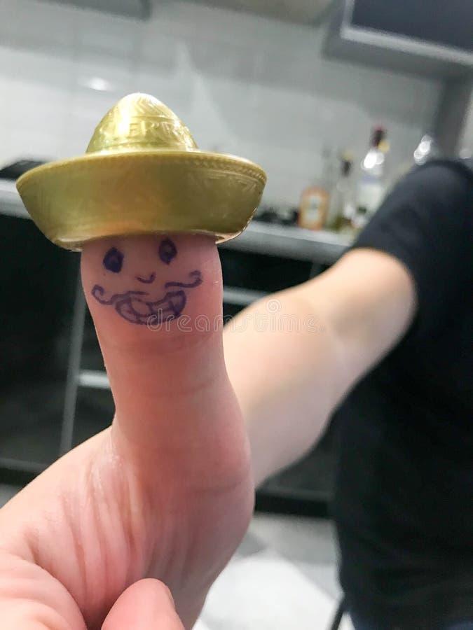 Kciuk, palcowy meksykanin w złocistym kapeluszowym sombrero z malującą rozochoconą rozochoconą twarzą z wąsami i oczy, obrazy stock