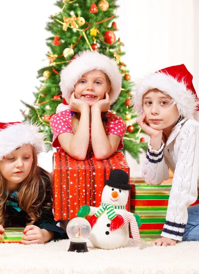 Kds sitzen neben Weihnachtsgeschenken stockfotografie