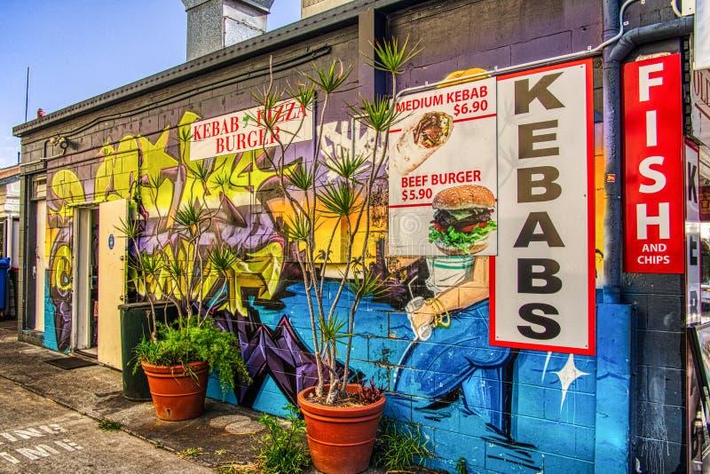 kebab商店和炸鱼加炸土豆片的边的墙壁上的街道画墙壁艺术 免版税库存图片