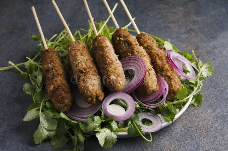 kebab特写镜头用香料,在黑暗的土气厨房用桌上的洋葱圈 库存图片