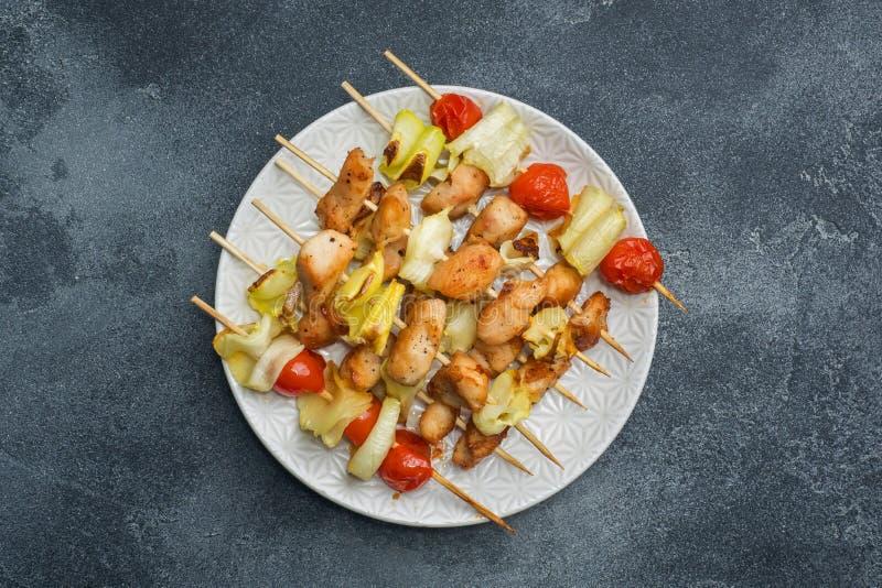 Kebab鸡、夏南瓜和蕃茄在串在板材 黑暗的桌拷贝空间 免版税图库摄影
