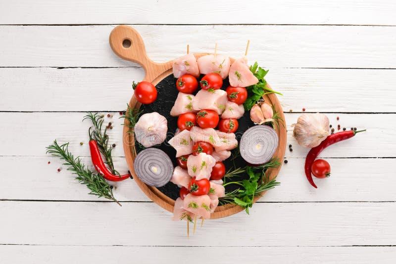 Kebab сырцового цыпленка shish с томатами вишни r На белой деревянной предпосылке стоковая фотография rf