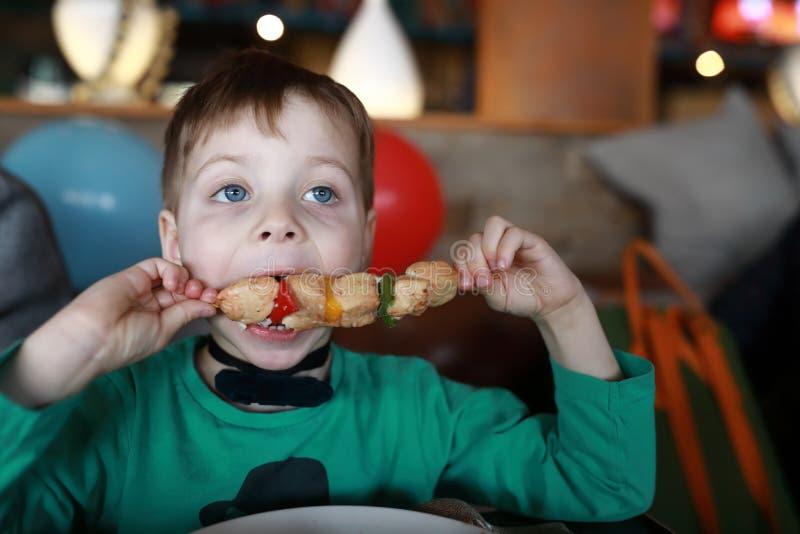 Мальчик есть kebab на протыкальнике стоковые изображения rf