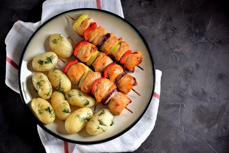 Kebab al forno del petto di pollo con la cipolla rossa, lo zucchini, il peperone e le patate bollite del bambino con aneto e olio fotografia stock