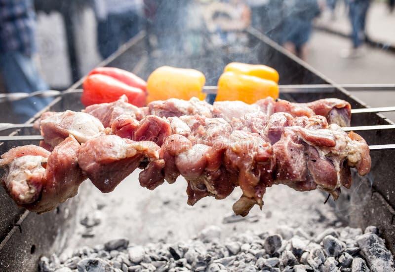 Kebab arrostito che cucina sullo spiedo del metallo Carne arrostita cucinata al barbecue con peperone dolce rosso e giallo fotografia stock libera da diritti