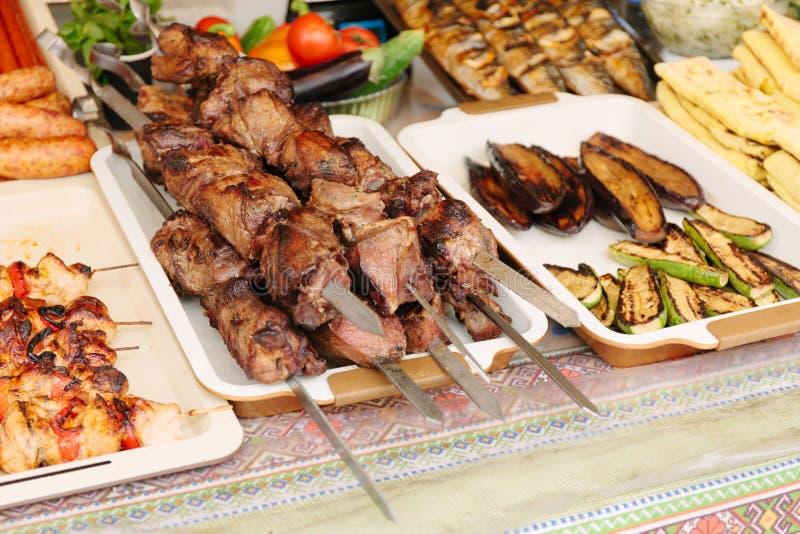 Kebab asado a la parrilla en el pincho del metal Escaparate de la comida de la calle imagenes de archivo