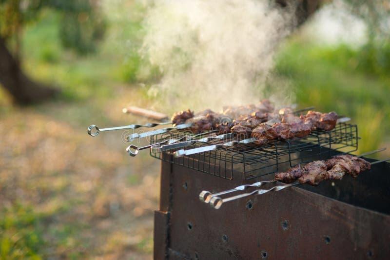 Kebab auf dem Grill Mariniertes shashlik, das auf einen Grillgrill über Holzkohle sich vorbereitet lizenzfreie stockfotos