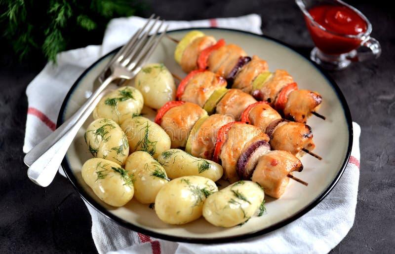 Kebab cocido de la pechuga de pollo con la cebolla roja, el calabacín, la pimienta roja y las patatas hervidas del bebé con eneld fotografía de archivo libre de regalías