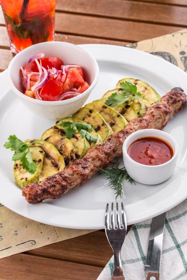 Kebab con el calabacín asado a la parrilla y los tomates frescos en la tabla de madera fotos de archivo