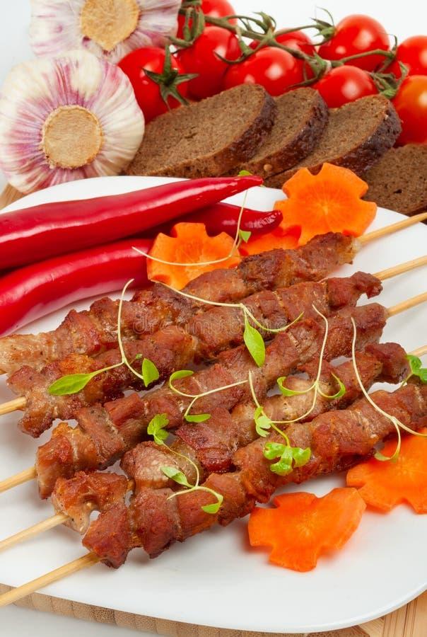 Kebab con las hierbas en una placa blanca imagenes de archivo