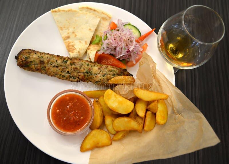 Kebab con un adorno de las patatas y de las verduras frescas fritas foto de archivo libre de regalías