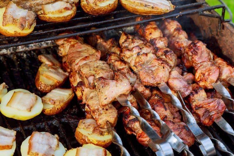 Kebab crudo che griglia sullo spiedo del metallo Torrefazione della carne al barbecue con le verdure Fette fresche di taglio del  fotografia stock