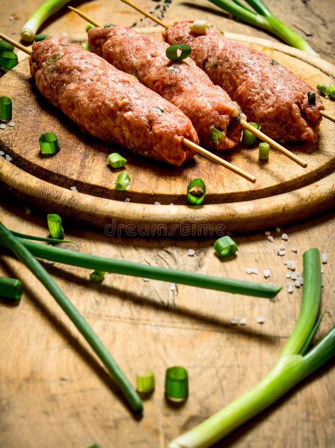 Kebab crudo con las cebollas verdes en el tablero imagen de archivo