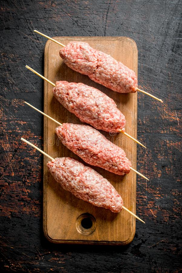 Kebab crudo de la carne picada en una tabla de cortar de madera imagenes de archivo
