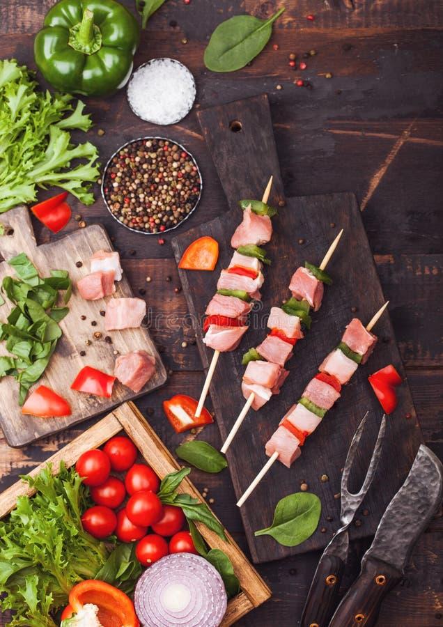 Kebab crudo del cerdo con paprika en la tajadera con las verduras frescas en fondo de madera con la bifurcación y el cuchillo Sal foto de archivo