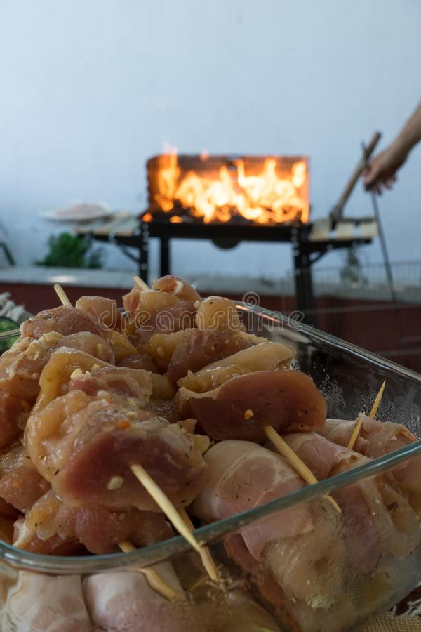 Kebab crudo del pollo antes de cocinar en el pincho del metal Ase a la parrilla en el carb?n de le?a y la llama, comida campestre imagen de archivo