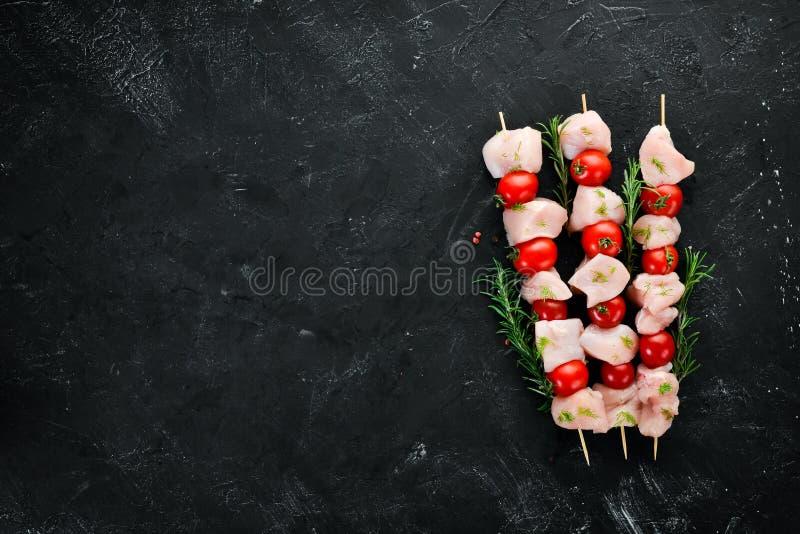 Kebab crudo del pollo con los tomates de cereza Barbacoa En un fondo de piedra negro imagen de archivo libre de regalías