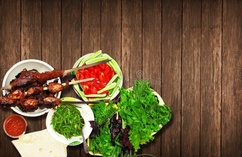 Kebab de la carne del cordero y de la carne de vaca con mentira apetitosa de las hierbas frescas en una tabla de madera foto de archivo libre de regalías