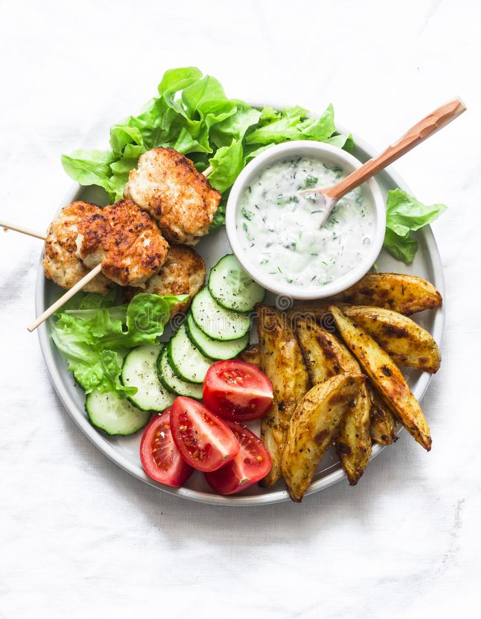 Kebab de las albóndigas, patata cocida rústica, verduras frescas y salsa de la hierba del yogur en el fondo ligero, visión superi foto de archivo libre de regalías