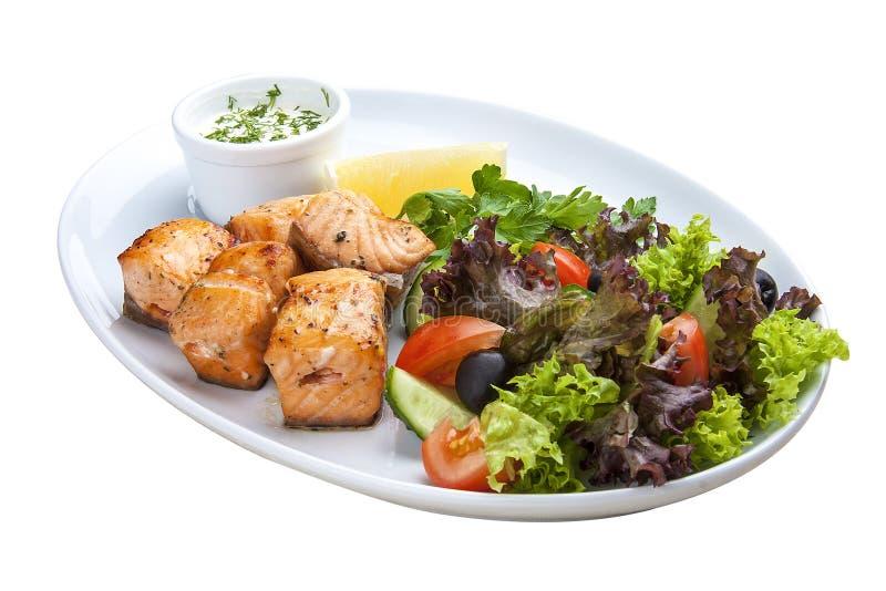 Kebab de salmones con las verduras y la ensalada En una placa blanca fotos de archivo libres de regalías