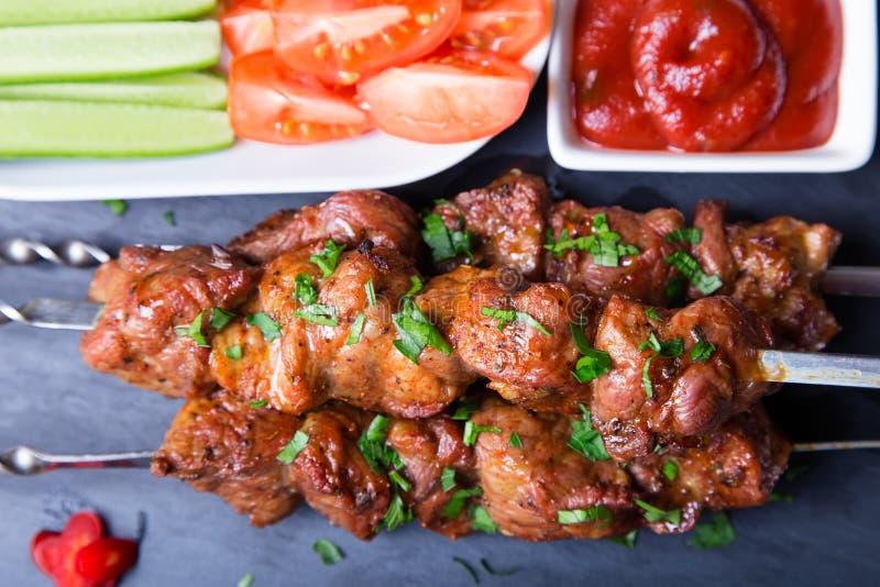 Kebab de Shashlik del cerdo de la carne en los pinchos con las verduras y la salsa de tomate imagen de archivo libre de regalías