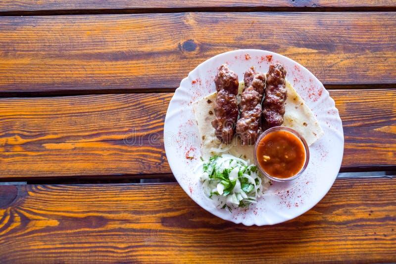 Kebab del luleh della parte su un piatto Piatto appetitoso sulla tavola di legno immagini stock