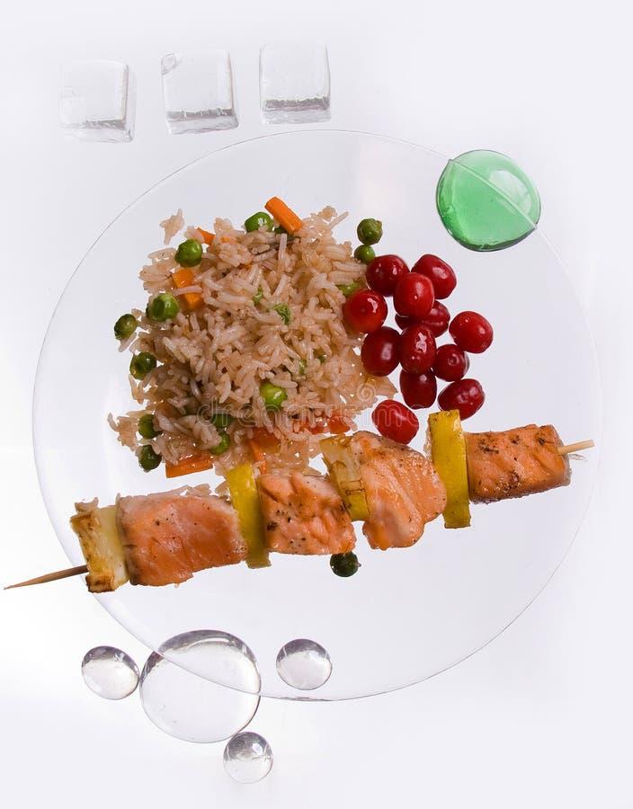 Kebab del pollo con arroz y verduras en un fondo blanco en un decoratet transparente de la placa con las piedras de cristal fotos de archivo