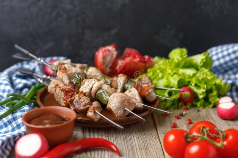Kebab delicati succosi di carne di maiale sugli spiedi presentati su un piatto e sugli ortaggi freschi Natura morta su un fondo d fotografia stock libera da diritti