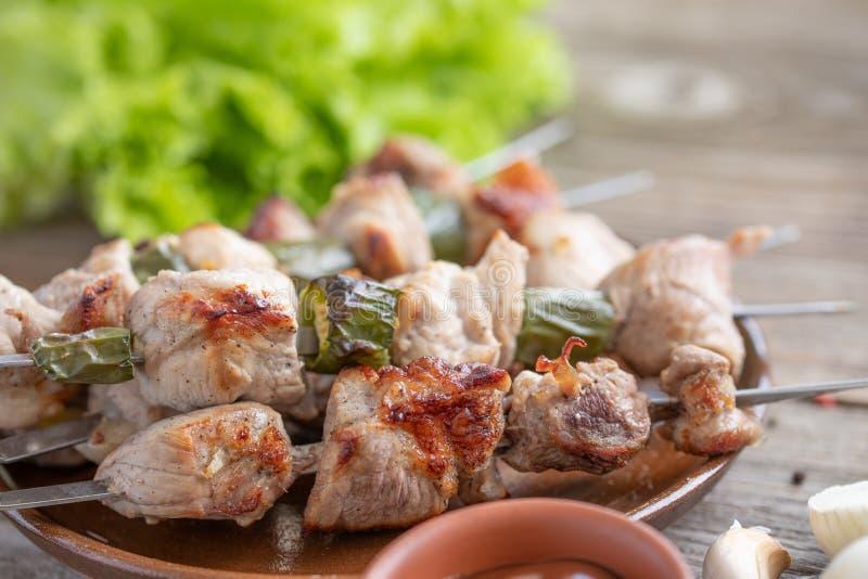 Kebab delicato da carne di maiale cucinata su un fuoco aperto e sulle foglie fresche della lattuga natura morta su un fondo di le fotografie stock libere da diritti