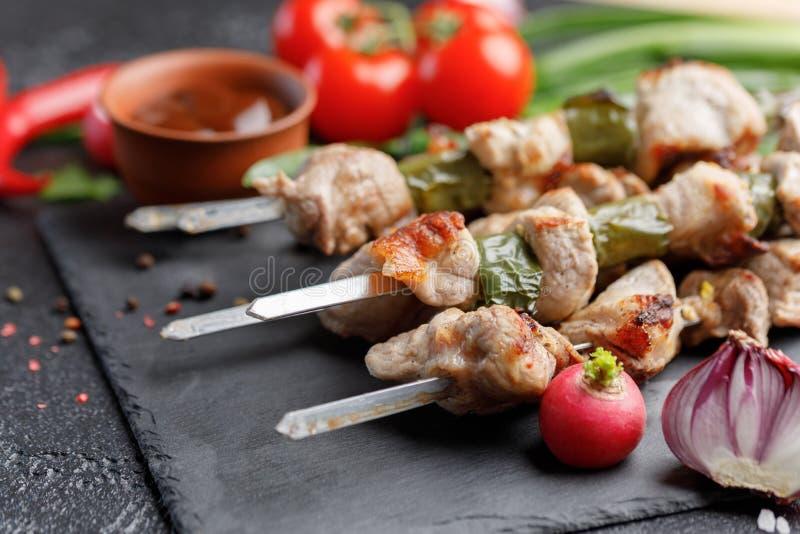 Kebab delicato da carne di maiale su un fondo nero La carne ha cucinato su fuoco e sugli ortaggi freschi aperti con salsa barbecu immagine stock libera da diritti