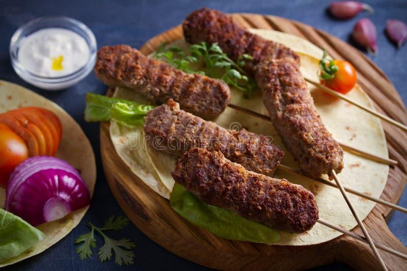 Kebab dell'agnello sul bordo servente con il pane della pita, le verdure e la salsa del yogurt immagine stock