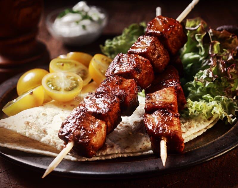 Kebab della carne di maiale con la tortiglia e l'insalata immagini stock libere da diritti