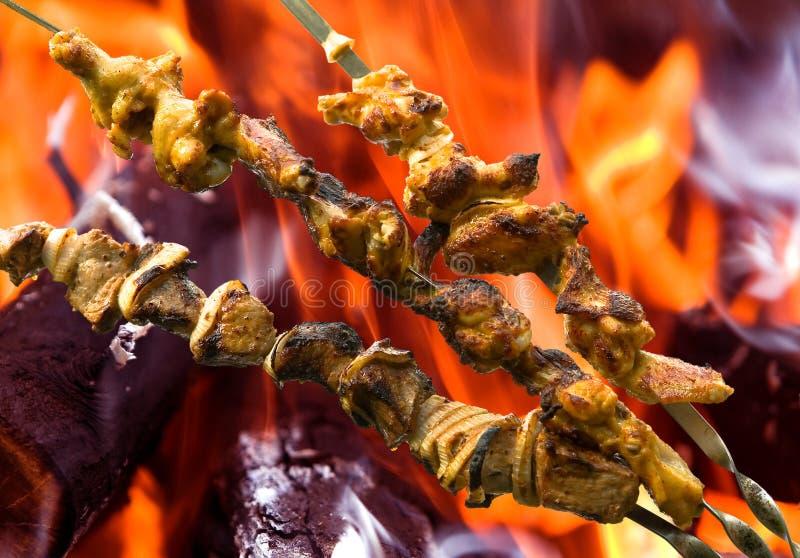 Kebab della carne di maiale e del pollo sui precedenti di fuoco immagini stock