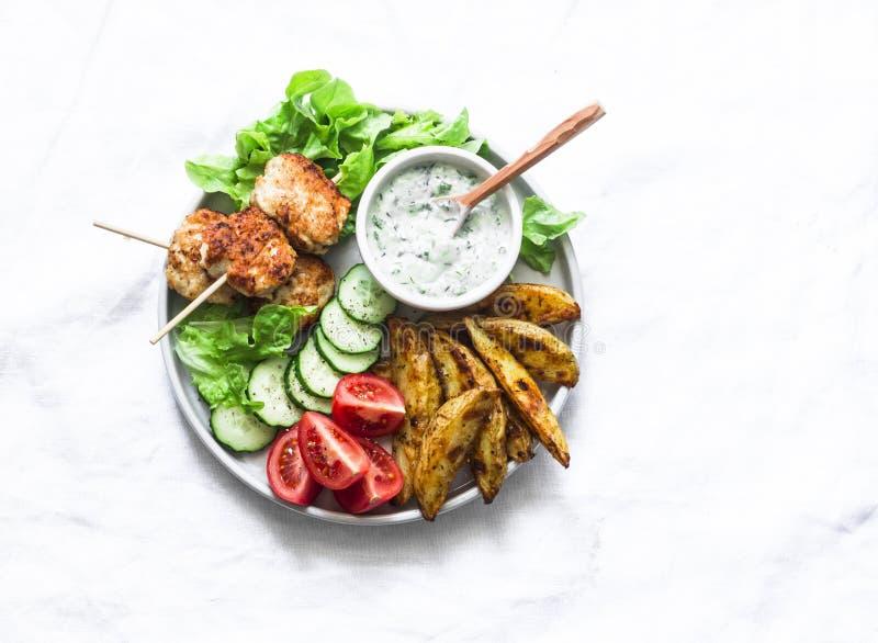 Kebab delle polpette, patata al forno rustica, ortaggi freschi e salsa dell'erba del yogurt su fondo leggero, vista superiore Pic fotografia stock