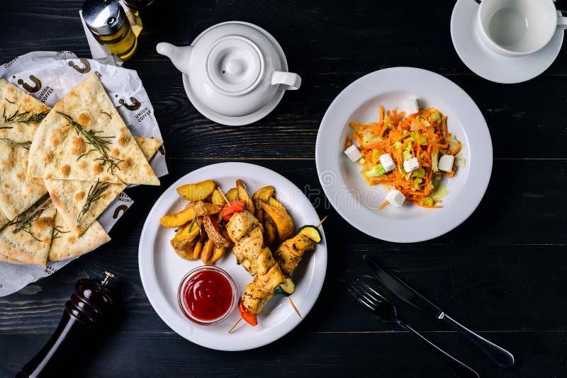 Kebab e salsa su una tavola nera in un ristorante del caffè fotografie stock libere da diritti