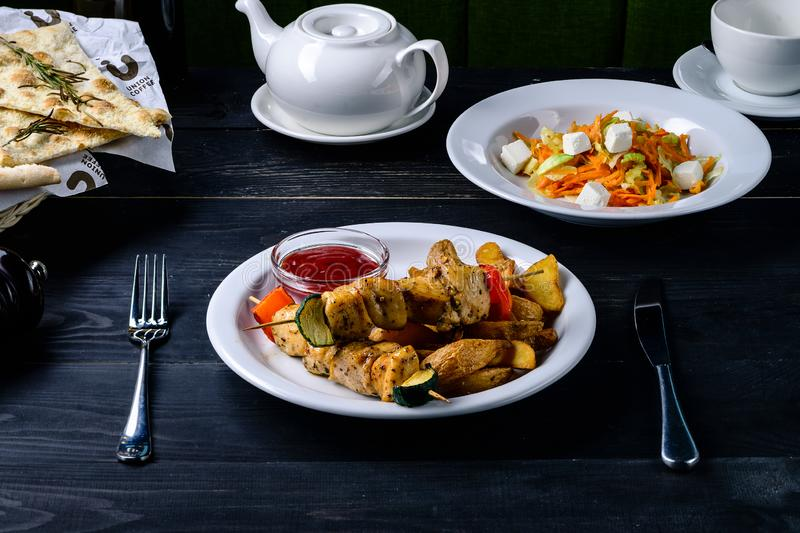 Kebab e salsa su una tavola nera in un ristorante del caffè immagini stock libere da diritti