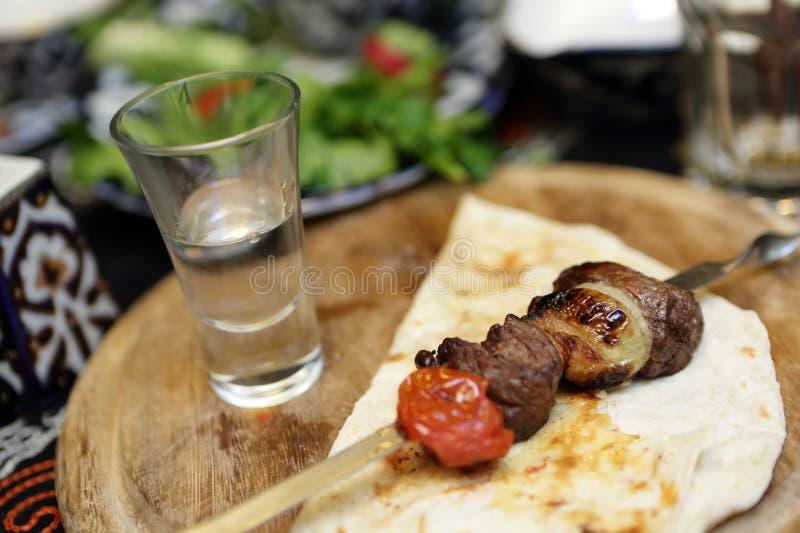 Kebab en los pinchos y el vidrio de vodka imagen de archivo