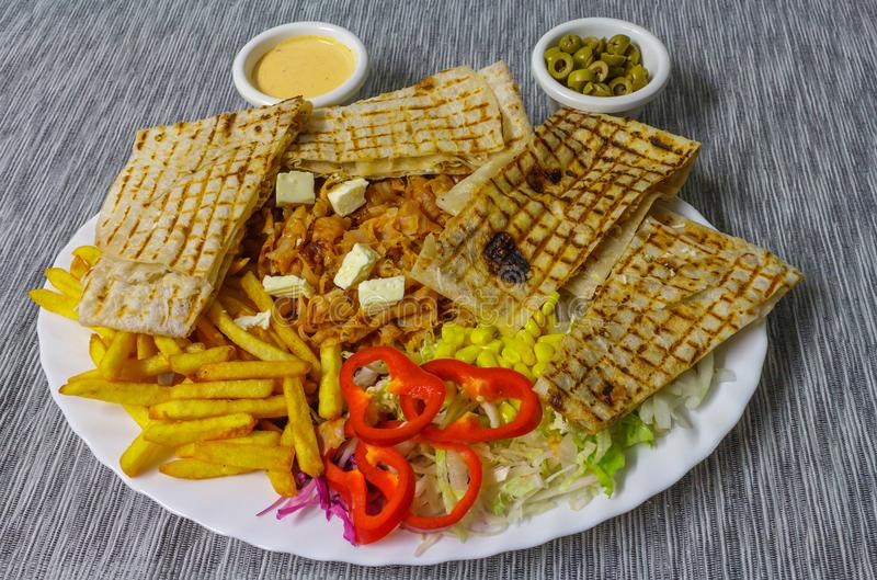 Kebab French fries baked tortilla and vegetables stock image