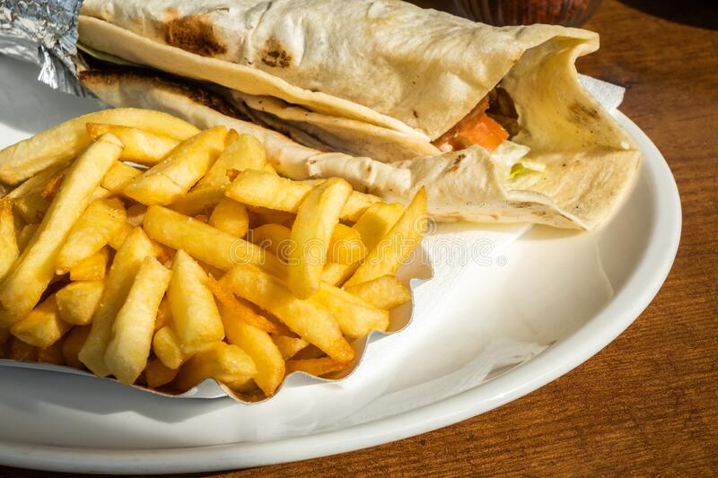 Kebab and French fries recipe on a white dish table. In an European country royalty free stock images