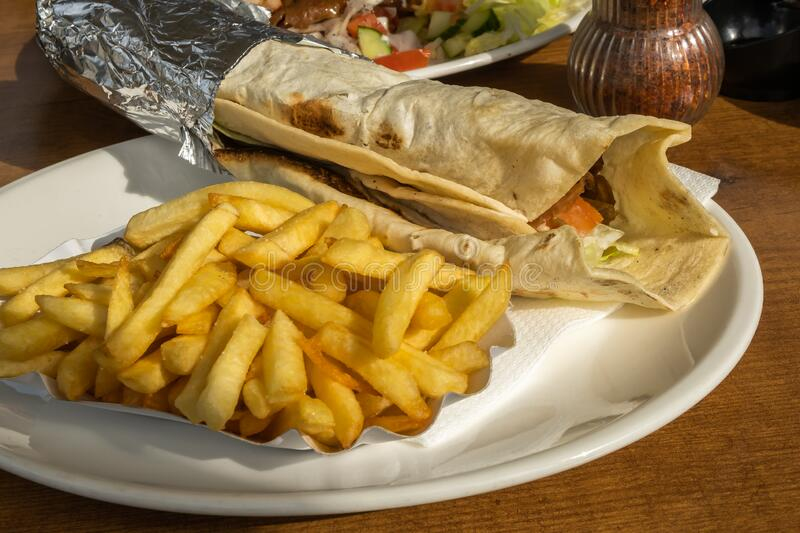 Kebab and French fries recipe on a white dish table in European country. Kebab and French fries recipe on a white dish table in an European country royalty free stock photos