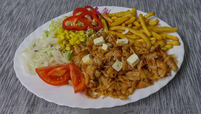 Kebab French fries and vegetables on a white plate royalty free stock image