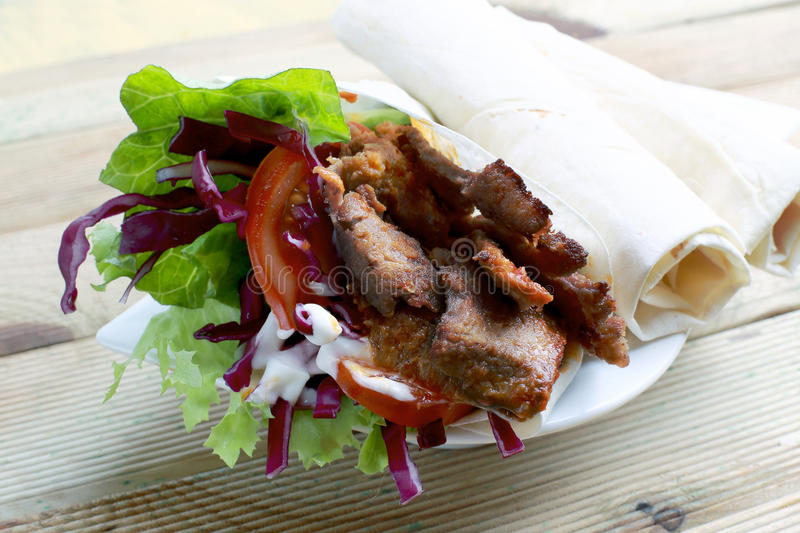 Kebab with lavash. A durum is a wrap that is usually filled with typical doner kebab ingredients. The wrap is made from lavash or yufka flatbreads stock photography