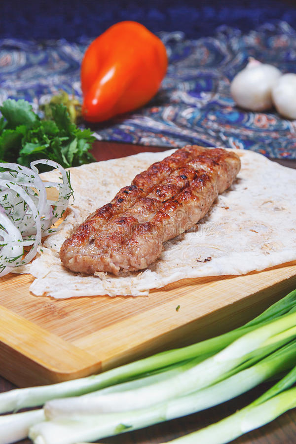 Kebab of minced meat. On wooden board with vegetables. close-up royalty free stock images