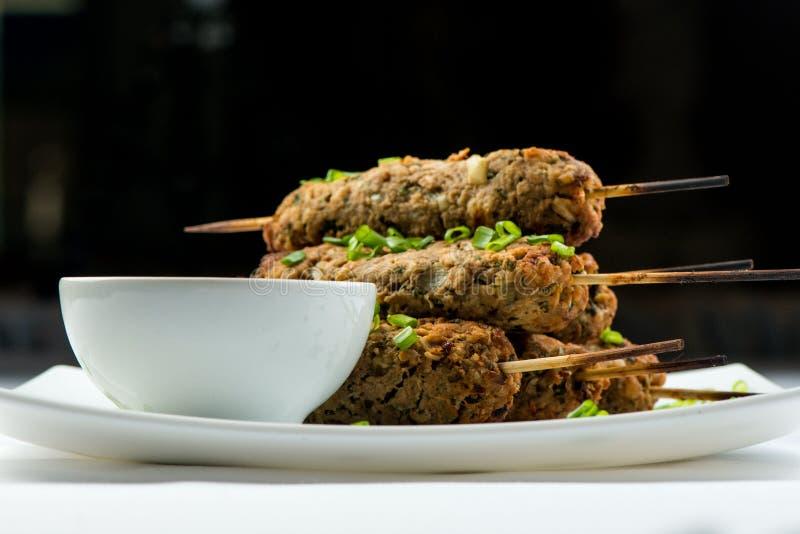 Kebab mit Kräutern auf einer weißen Platte stockfoto
