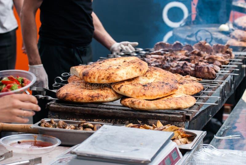 Kebab och pitabröd på gallret i röken, närbild royaltyfri fotografi