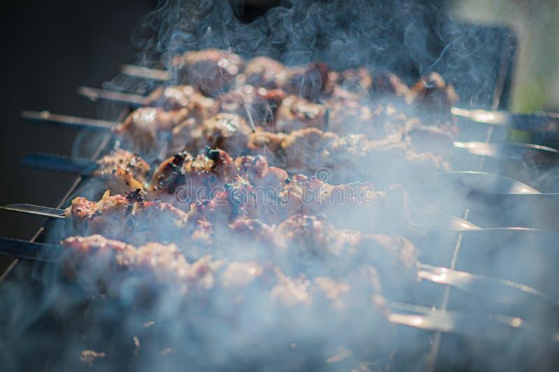 Kebab que cocina en aire abierto en verano pinchos de la barbacoa fritos en la parrilla en el humo de los carbones imagen de archivo libre de regalías